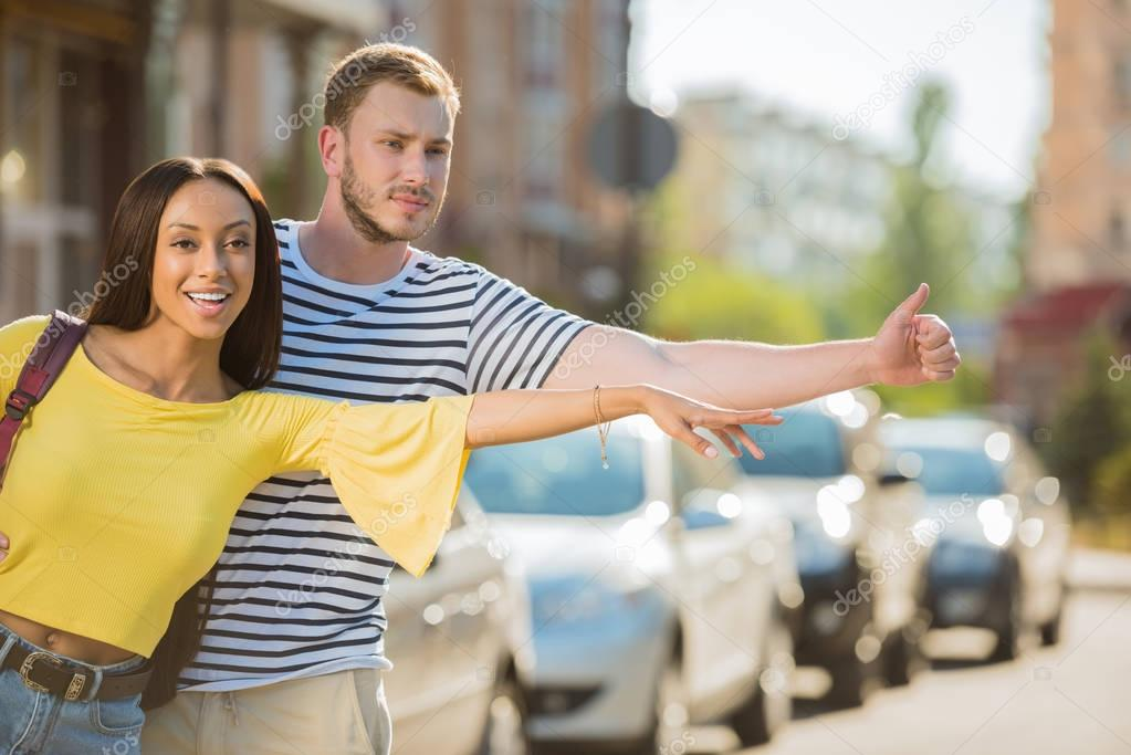 Multiethnic couple hailing taxi