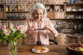 Fotografie žena fotografování talíř s jídlem v kuchyni