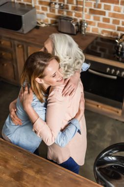 two women hugging in kitchen