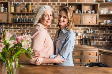 two women hugging in kitchen