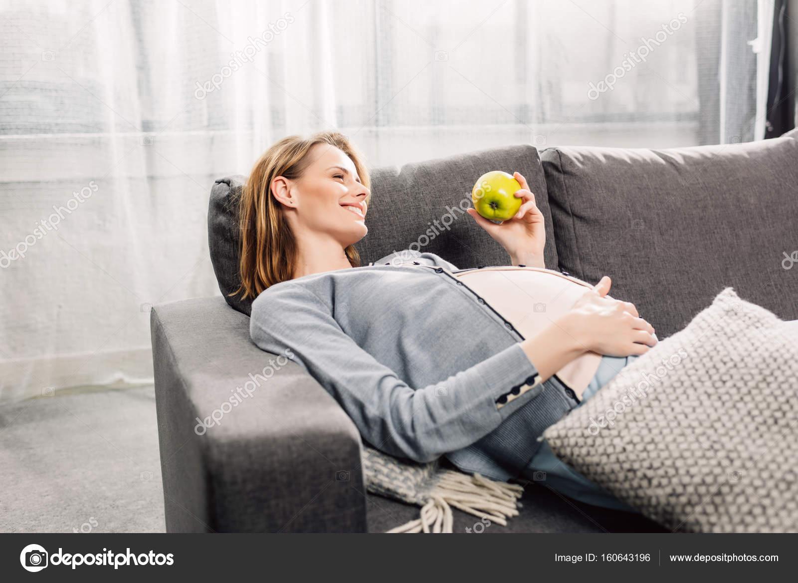 έγκυος γυναίκα στηρίζεται σε γκρι καναπέ — Φωτογραφία Αρχείου ... b3393d1fe07
