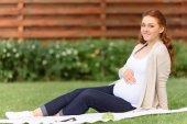 Terhes nő ül a gyep