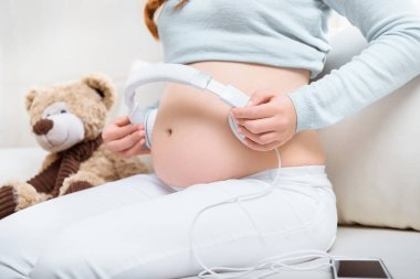 pregnant woman with headphones on belly