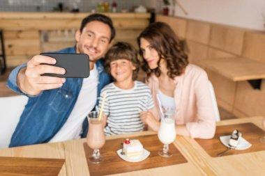 Family taking selfie in cafe