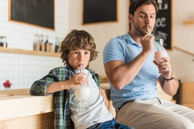 son and father drinking milkshakes