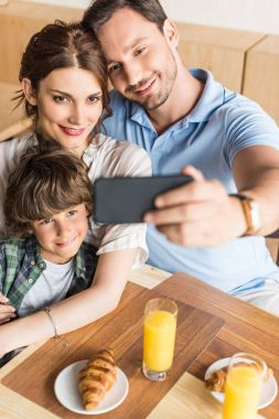 family taking selfie in cafe