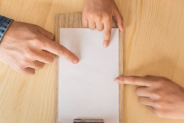 family pointing at blank paper