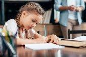 malá dívka psaní domácích úkolů