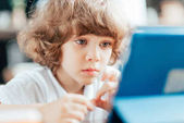 thoughtful curly kid using tablet