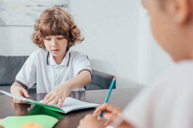 Boy doing homework with sister