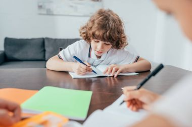 boy doing homework with sister