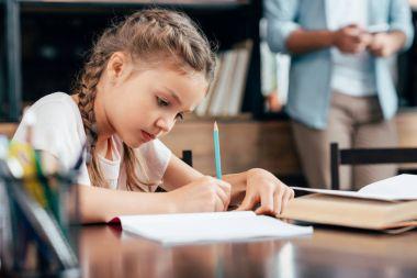 little girl writing homework
