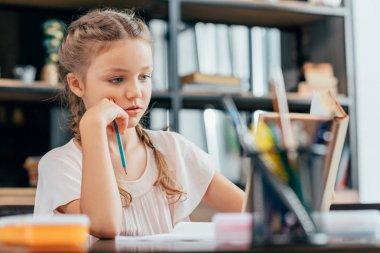 Focused cute little girl doing homework stock vector
