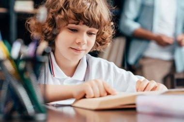 Smiling little boy reading old book for homework stock vector