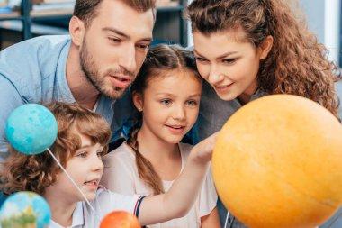 family exploring solar system model
