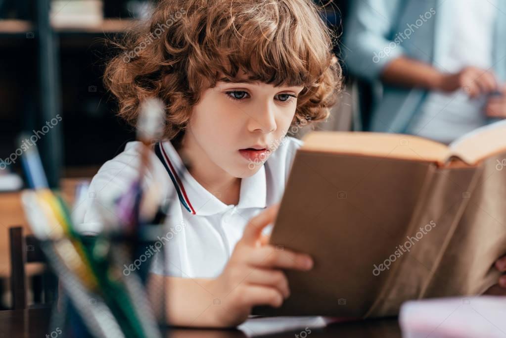 Little boy reading book for homework stock vector