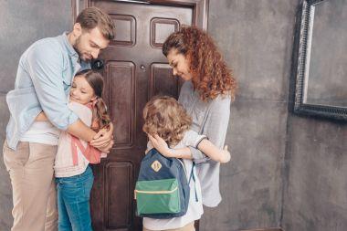 Parents hug kids before school