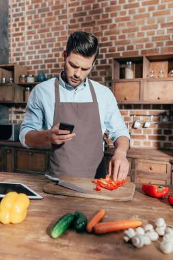 man using smartphone while cooking