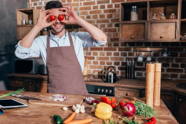 Man covering eyes with tomatoes