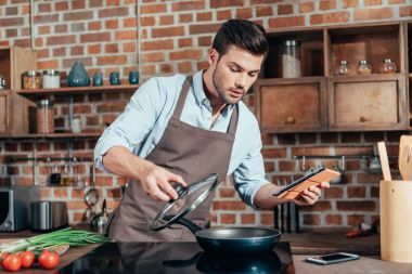 man cooking with tablet