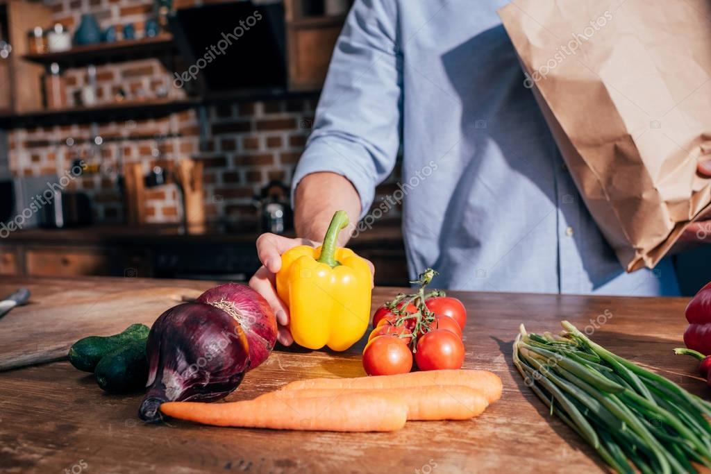 man unpacking vegetables