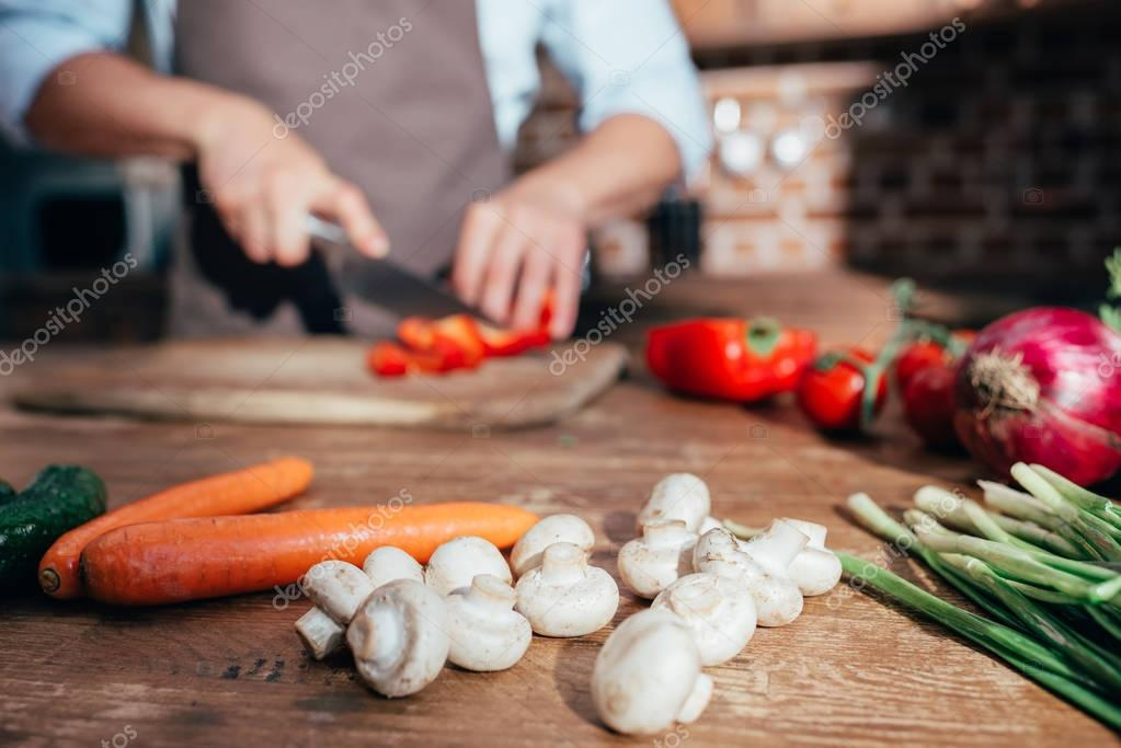 vegetables on kitchen with man cooking