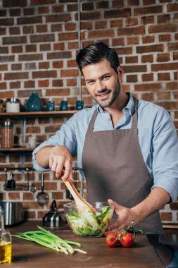 Handsome smiling man making salad stock vector