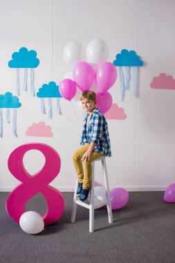 Happy little boy sitting on stool with balloons and smiling at camera at birthday party stock vector