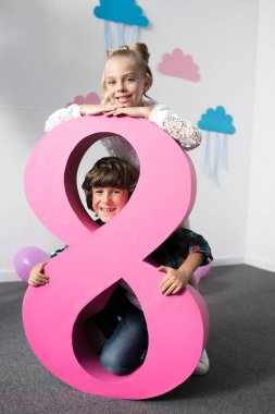 Adorable happy kids posing with decorative pink number eight at birthday party stock vector