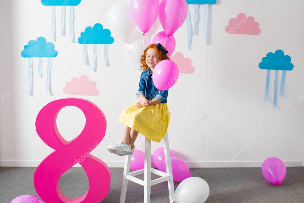 girl with balloons at birthday party