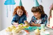 Fotografie jungen und Mädchen am Geburtstagstisch