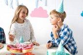 Fotografie Junge und Mädchen am Geburtstagstisch