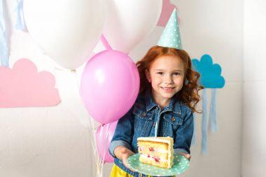 girl holding birthday cake