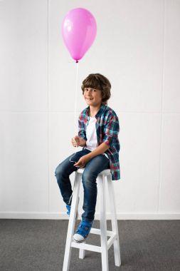 little boy holding balloon
