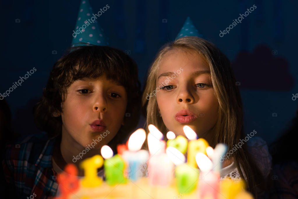 kids blowing candles on birthday cake