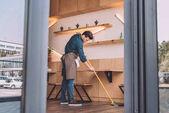 Arbeiter putzt Fußboden mit Kehrmaschine