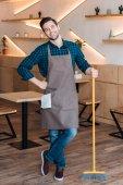 pracovník s koštětem v kavárně