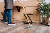 dělník čištění podlahy s koštětem