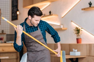 man having fun with broom in cafe