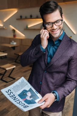 businessman with newspaper talking on smartphone