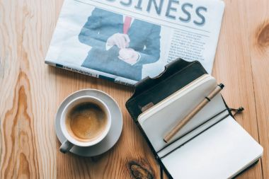 cup of coffee, newspaper and notebook on table
