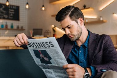 businessman reading newspaper in coffee shop