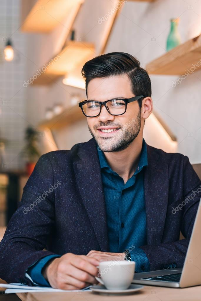 smiling businessman with laptop in cafe