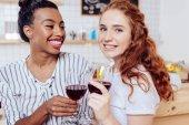 multiethnic girls drinking wine