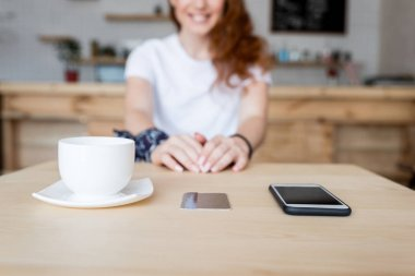 coffee cup, smartphone and card on table