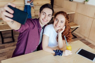 Happy young couple taking selfie while sitting together in cafe stock vector