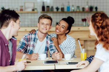 multiethnic couple with friends in cafe