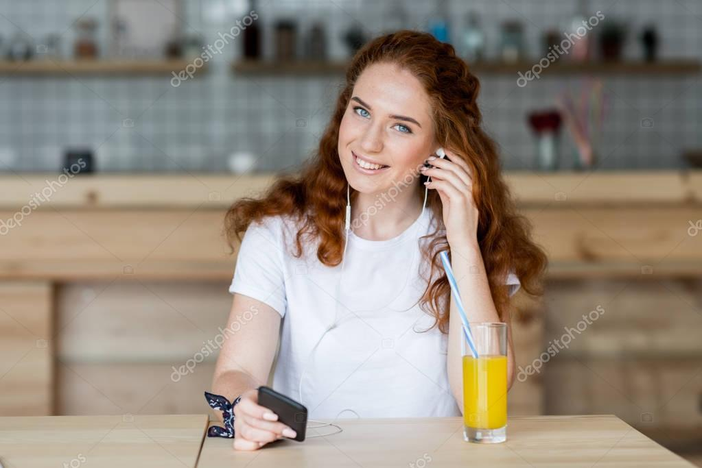 girl in earphones drinking juice