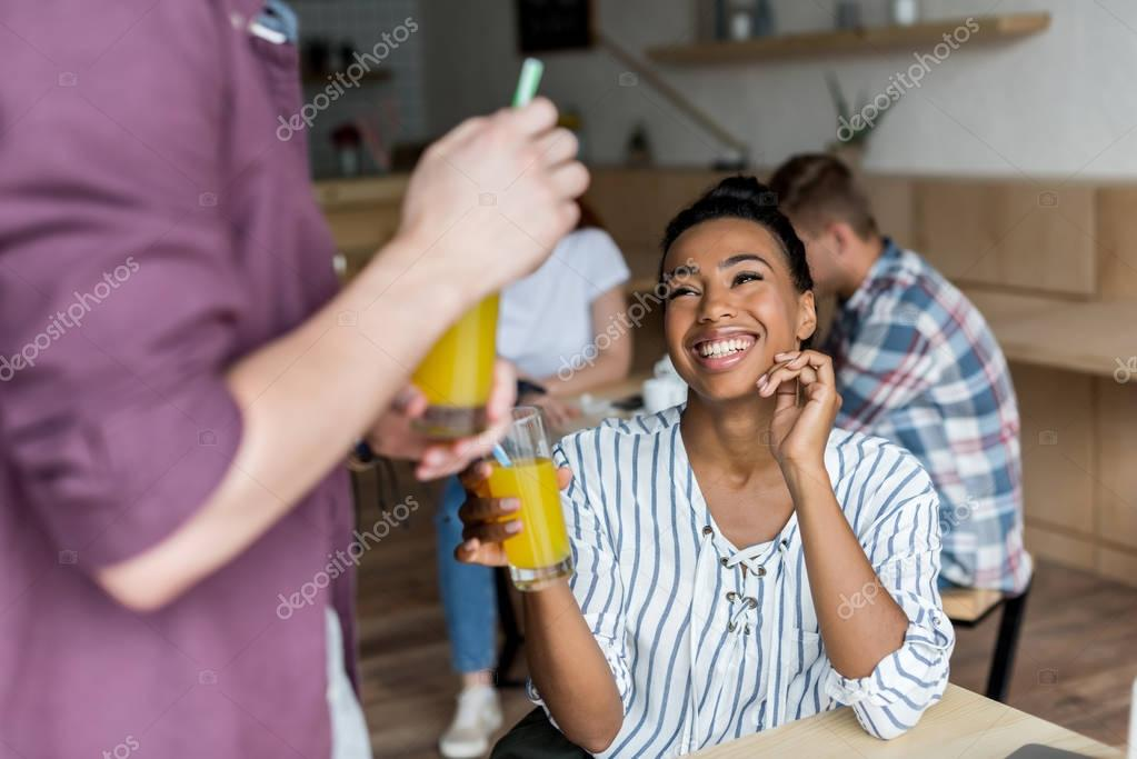multiethnic couple drinking juice
