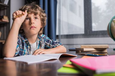 Portrait of thoughtful little boy looking away while doing homework at home stock vector